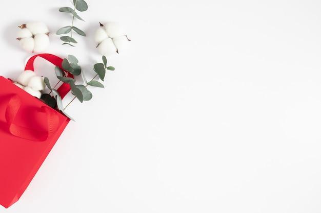 白い背景の上のユーカリと綿の花の枝と赤いギフトバッグ