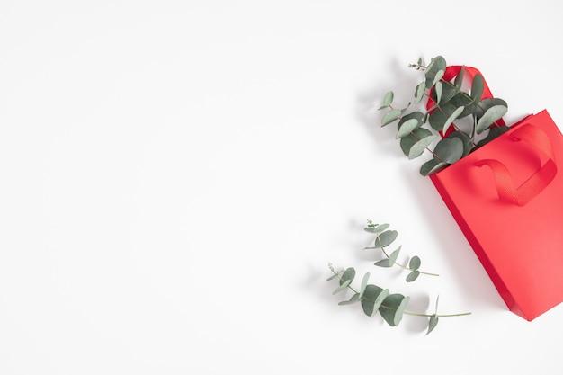白い背景の上のユーカリの枝と赤いギフトバッグ