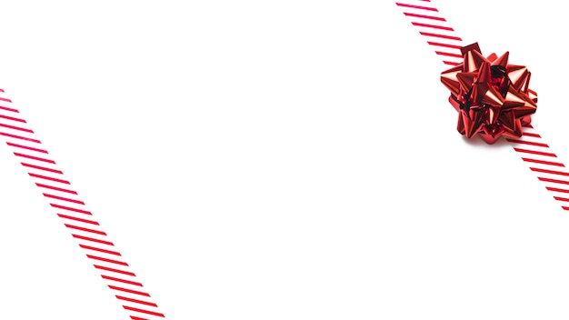Arco rosso del regalo con i nastri sulla tabella bianca