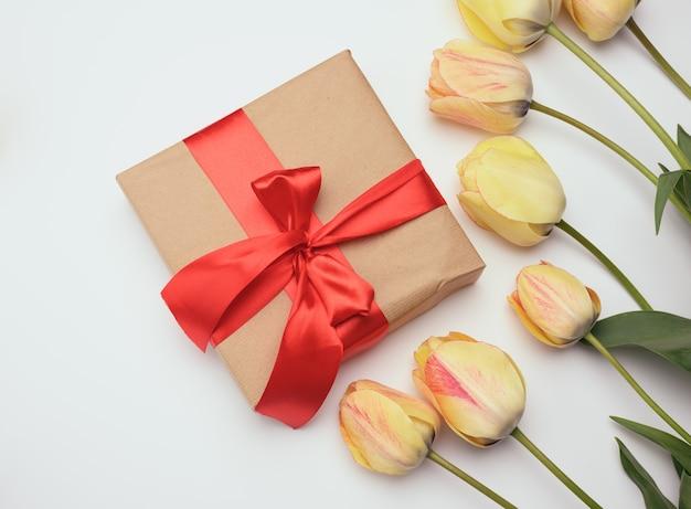 Красная подарочная коробка и желтые тюльпаны на белой поверхности, праздничной поверхности, вид сверху