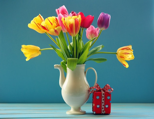 Red gift box and bouquet of multicolored tulips in white ceramic tea pot