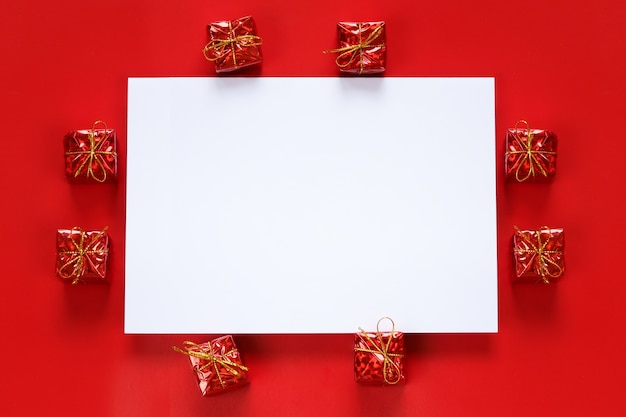 Red gift box and empty paper note on red background.