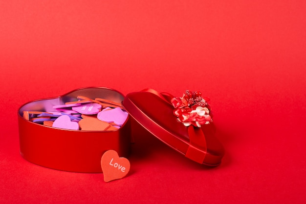 Red gift box full of multicolored paper hearts