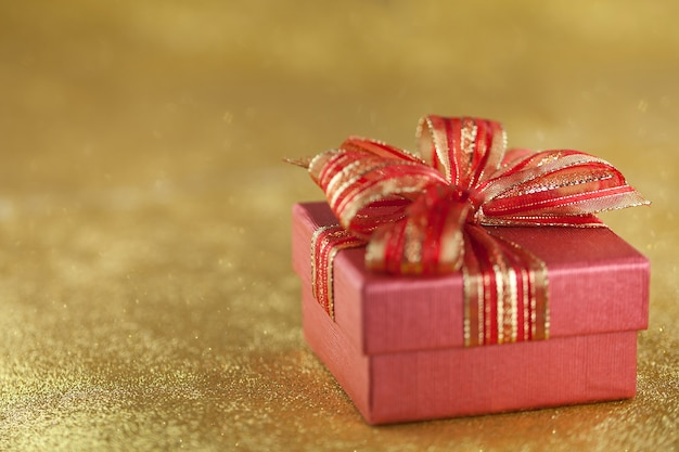 Red gift box on glitter gold background
