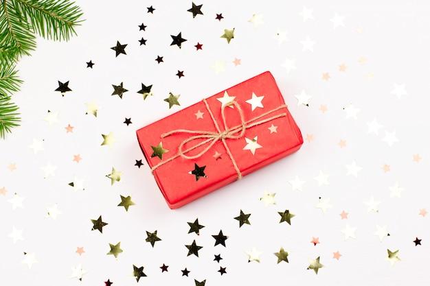 Красная подарочная коробка, золотое конфетти на белом. рождественская открытка