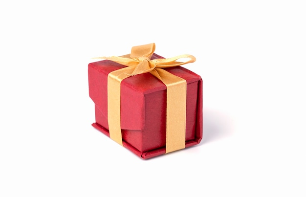 Red gift box and golden ribbon on white and bokeh background, happy birthday and happy new year concept.