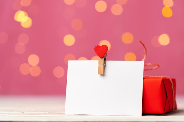 Red gift box and greeting card on pink background close up