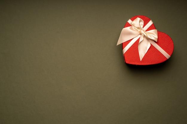 빨간색 선물 상자, 하트 모양, 녹색 배경에 리본으로 묶여, 축하, 선물, 휴일, 놀람 프리미엄 사진