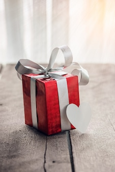 Red gift box and heart on white wooden table