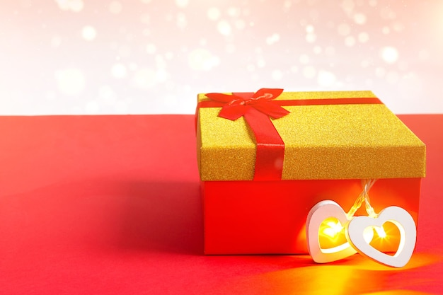Red gift box and heart with a glowing lamp inside