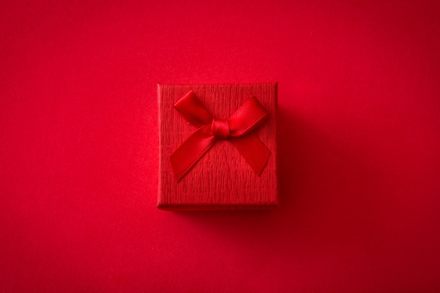 Красная подарочная коробка на красном фоне вид сверху