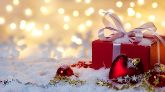 Red gift box on snow with bokeh background