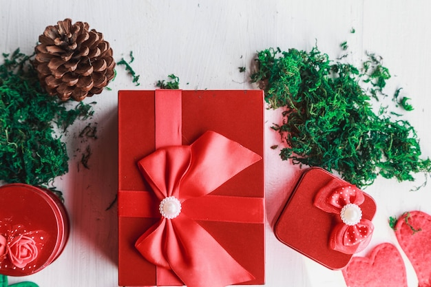 クリスマスの日の白い木製の背景に赤いギフトボックス