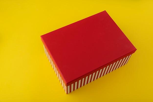 Красная подарочная коробка на желтом фоне. скопируйте пространство. макет.