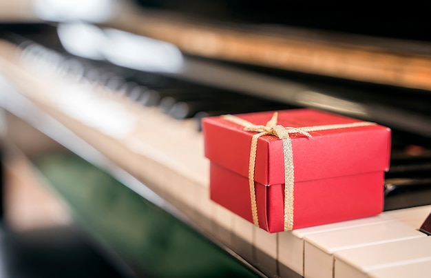 Red gift box on piano keyboard for background.