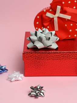 Red gift box on pink wall, festive wall, close up