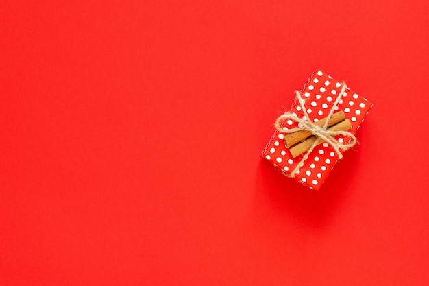 Red gift box in polka dots with cinnamon on a red background, merry christmas and happy new year concept