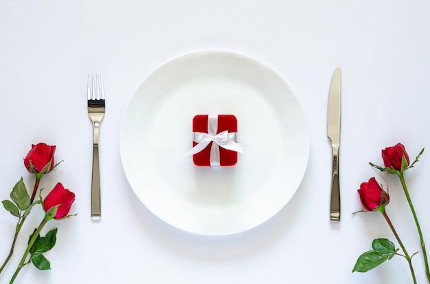 Красная подарочная коробка кладет тарелку на белый стол для концепции дня святого валентина.