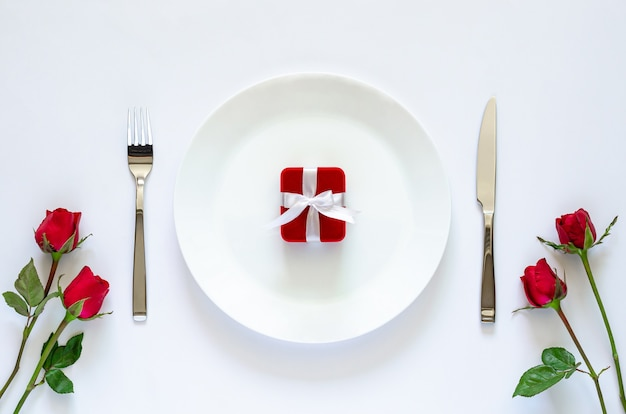 Red gift box puts on plate on white table for valentine's day concept.