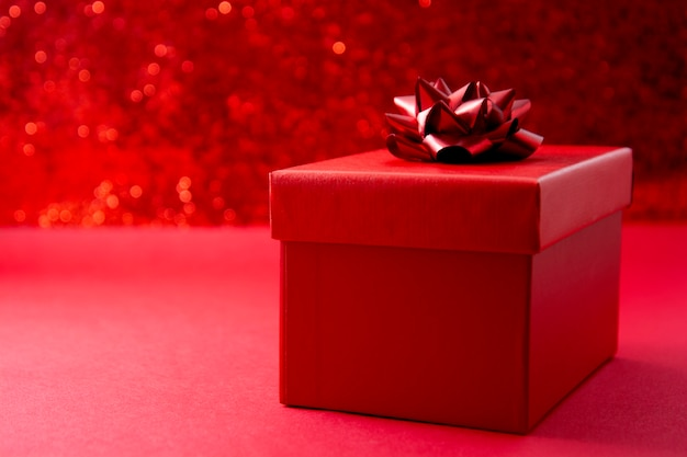 Red gift box on red background with copy space