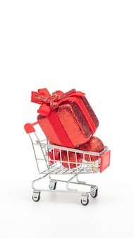 Red gift box in a shopping cart on a white background.