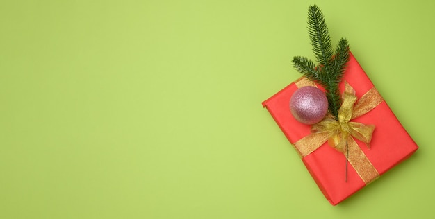 Red gift box tied with red ribbon on a green background, top view. festive backdrop, copy space