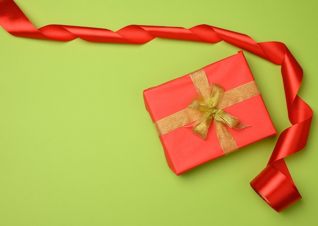 Red gift box tied with a silk ribbon on the green background, top view. festive backdrop