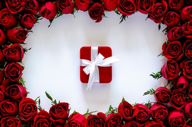 Red gift box on white background with roses frame for anniversary and valentine's day concept.