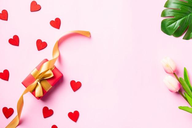 Красная подарочная коробка с золотой лентой-бантом и деревянными красными сердечками для любви