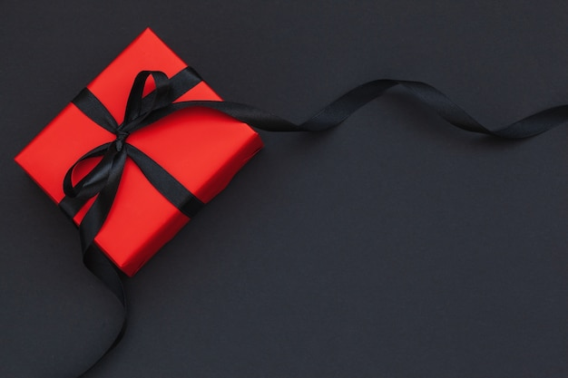 Red gift box with black ribbon on black background