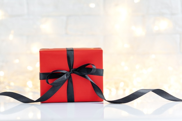Red gift box with black ribbon on white light background with copy space for text.