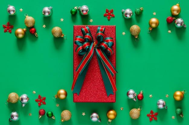 Красная подарочная коробка с лентой банта и рождественскими украшениями безделушек на зеленом фоне.
