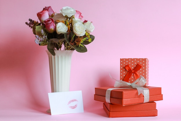 Red gift box with colorful rose on vase and kiss mark on white envelope isolated on pink background