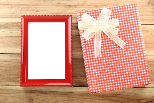 Red gift box with empty wooden picture frame on wood background.