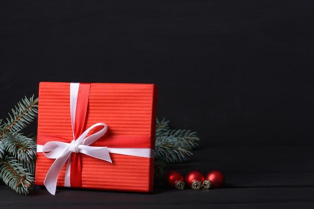 Красная подарочная коробка с елкой и стеклянными шарами изолированы