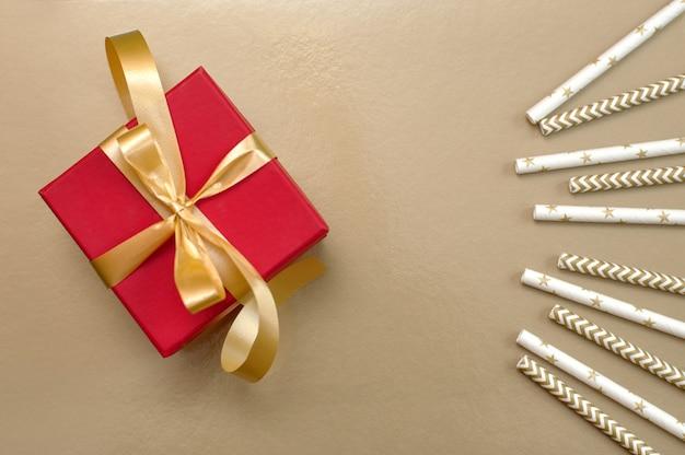 Красная подарочная коробка с золотой лентой, бантом и соломкой