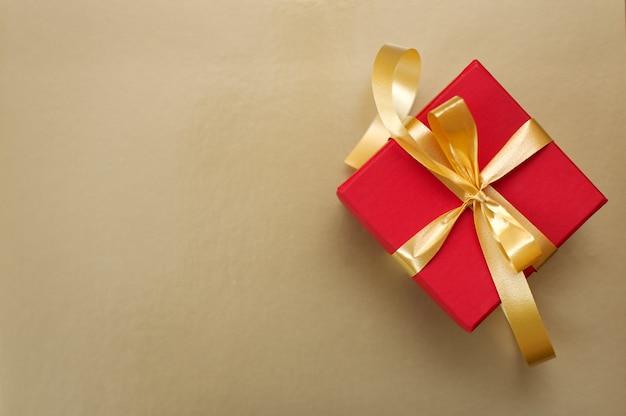 Красная подарочная коробка с золотой лентой и бантом