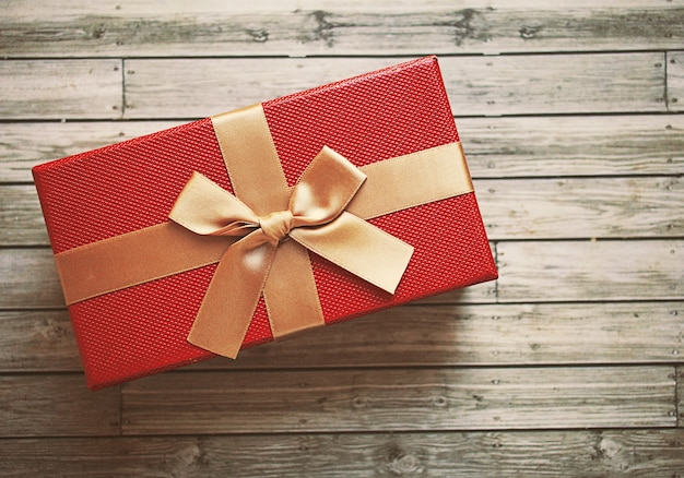 Red gift box with gold ribbon, retro filter effect