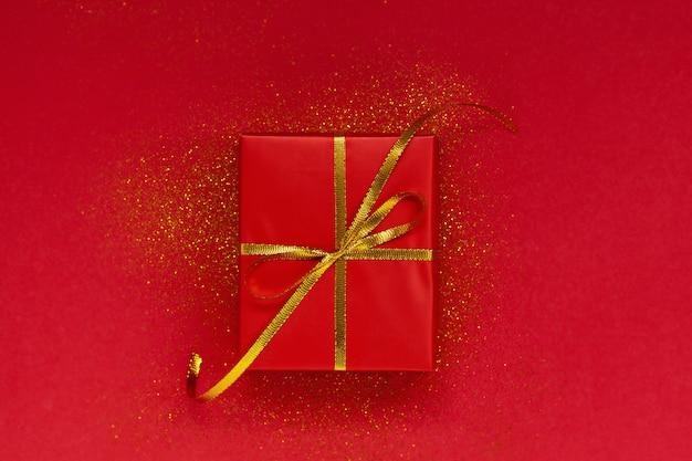 Красная подарочная коробка с золотым бантом на красном фоне с блестками.
