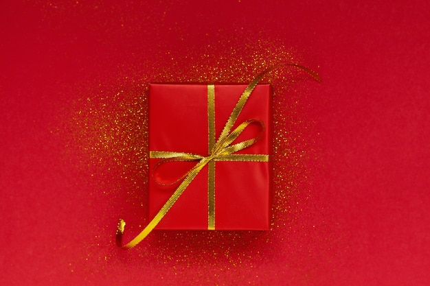 Red gift box with golden bow on red background with sparkles.