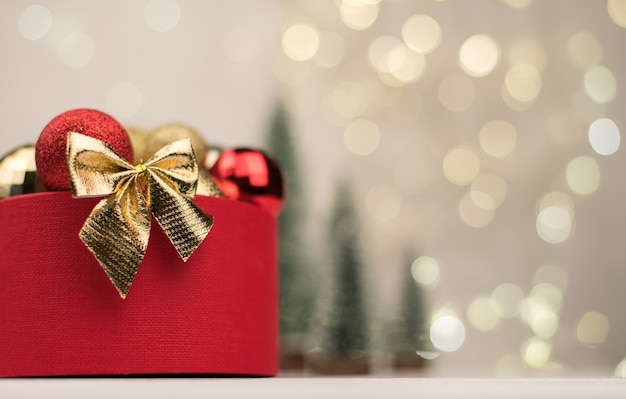Red gift box with a golden bow with christmas trees