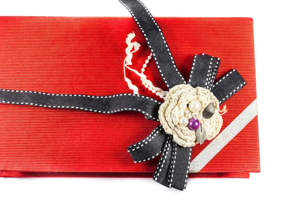 Red gift box with golden ribbon over white background