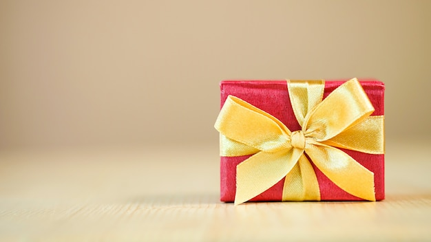 Red gift box with golden ribbon on wooden table background for merry christmas and happy new year. holiday and party