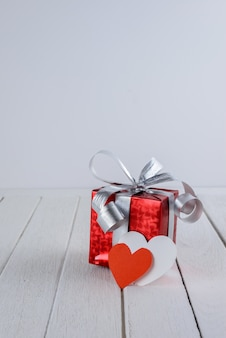 Red gift box with heart shape on white wooden table