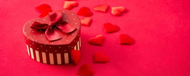 Красная подарочная коробка с сердечком на красном.