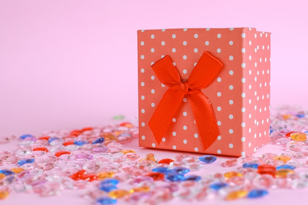 Red gift box with marbles on pink background
