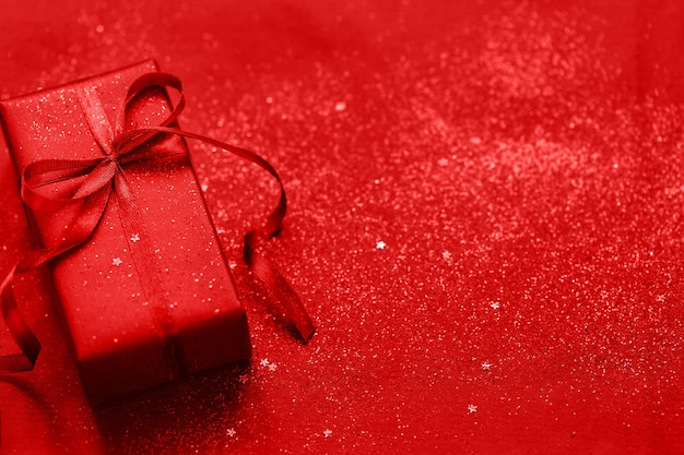 Red gift box with red bow on red shiny glitter holiday beautiful background
