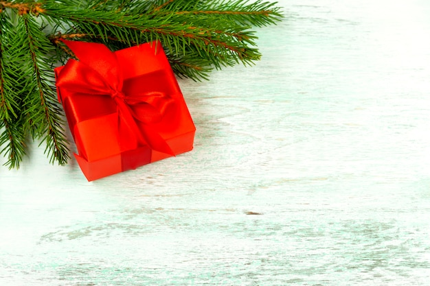 Red gift box with a red bow on a wooden floor near fir branches. view from above. christmas composition