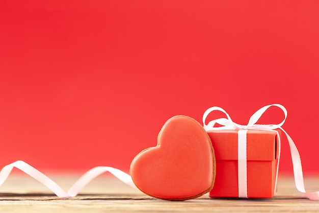 赤い背景にバレンタインデー、母の日、誕生日のための赤いハート型のジンジャーブレッドが付いた赤いギフトボックス。