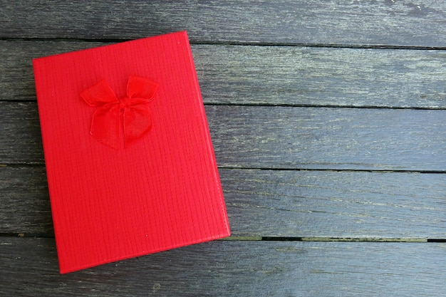 A red gift box with red ribbon on the black wooden background